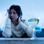 A depressed woman sits with a glass of wine in front of her.