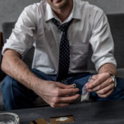 A professional sitting on a couch preparing lines of cocaine.